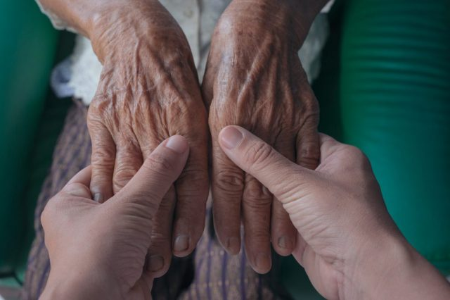 Young woman holding an elderly woman's hand.