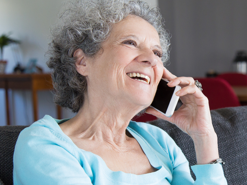Retrat de l'àvia feliç asseguda al sofà i parlant per telèfon