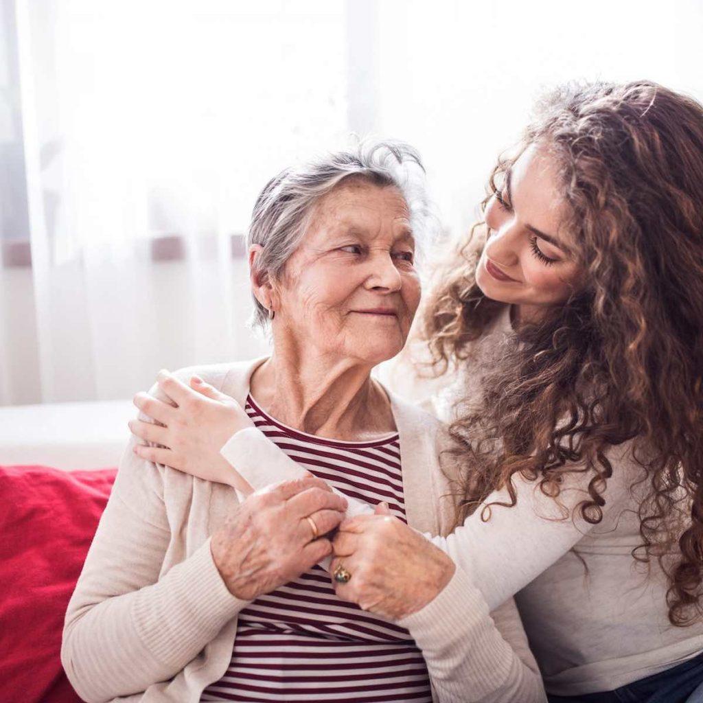 Dona jove i afectuosa feliç i somriure abraçant una dona gran